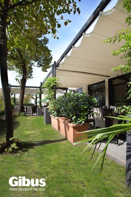 Wall-mounted motorized pergola with sliding cover MEDISOLAFLY FRONT LEANING by GIBUS
