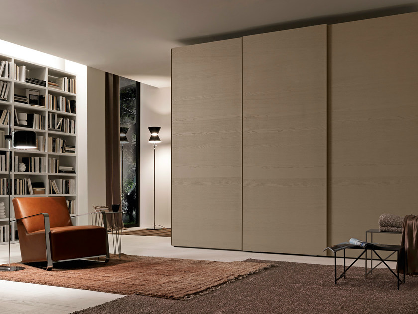 Wardrobe with Meg sliding doors, marrone daino color wood panels and built-in handles lacquered in a matching finish.