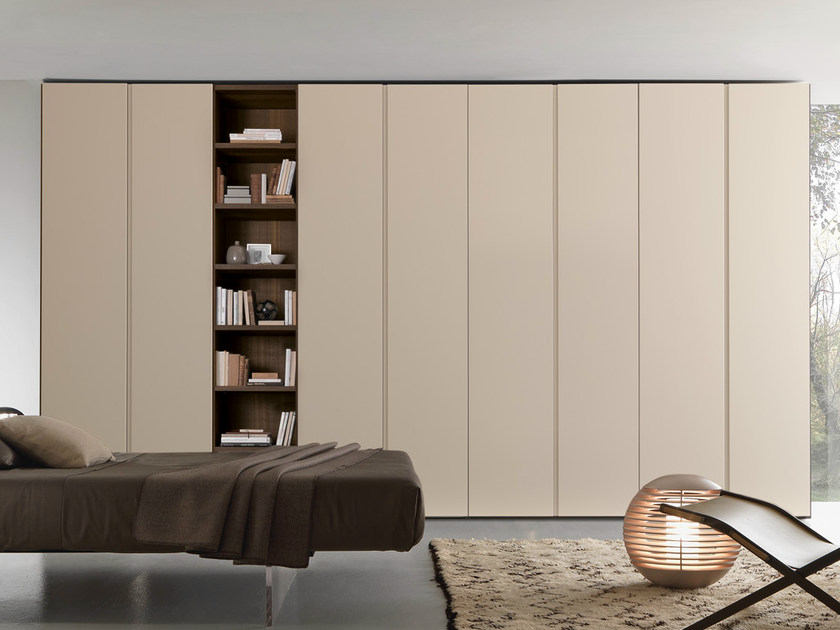 "Wardrobe with Beverly swing doors in matt corda lacquer; bookcase niche in ""aged"" tabacco oak. The concave handle is integrated in the entire height of the door."