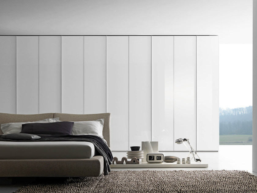 Wardrobe with Glass swing doors in bianco candido lacquered glass with matt lacquered profile; the handle incorporated in the frame is lacquered to match the door.