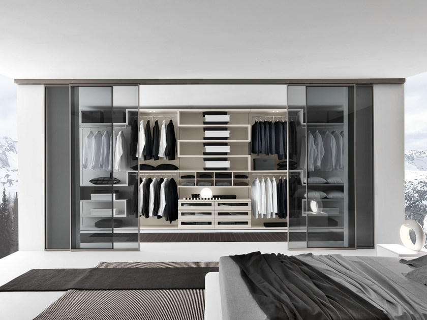 Walk-in-closet with Lino melamine interior accessories, sliding doors with a titanium finish aluminium frame and clear grigio glass; 2-ways runner applied to the ceiling.