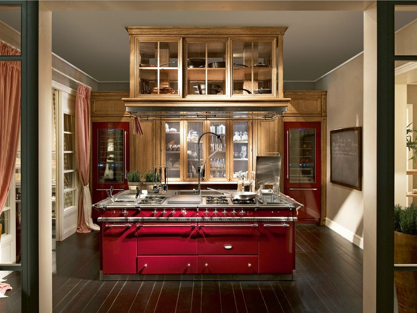 "The Burgundy red ""Lacanche"" kitchen block lies at the heart of the Monterey kitchen, in chromatic coordination with the two in-built fridges, fitted with transparent glass doors."