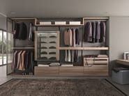 Varius free walk-in-closet in eucalipto melamine. The 1310-mm high storage unit is provided with glass shelves with mirrored back panels and doors in clear grigio glass.
