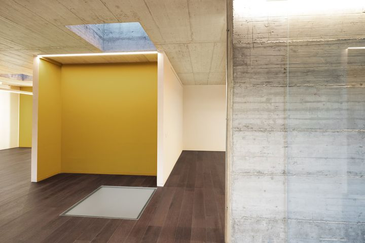 Gioco di contrasti: cemento, parquet, marmo e metallo black