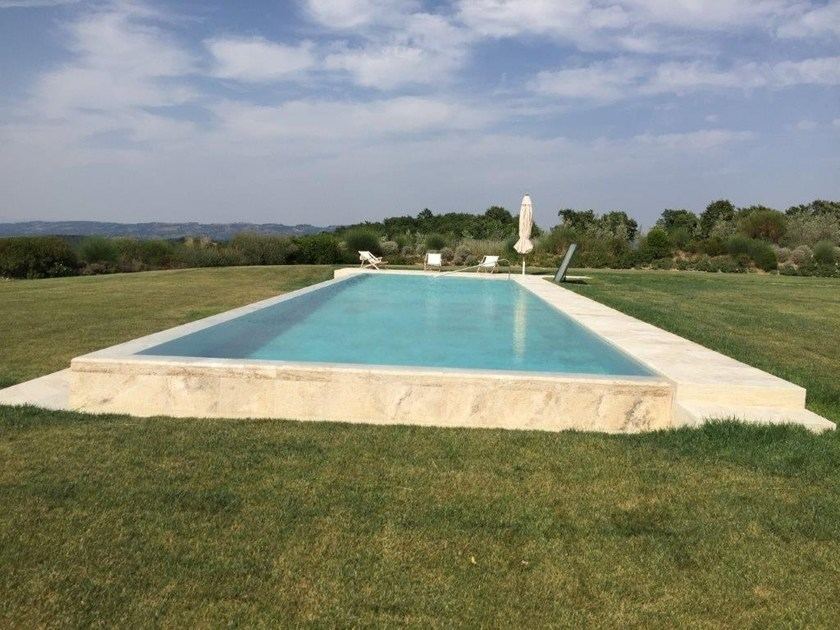 Infinity travertine swimming pool with waterfall Infinity swimming pool by INDALO PISCINE
