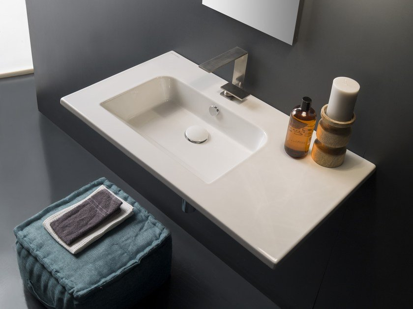 Wall-mounted ceramic washbasin with integrated countertop ETRA | Washbasin with integrated countertop by Scarabeo Ceramiche